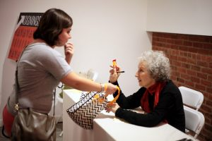 An attendee presents bestselling author Margaret Atwood with her choice of candy.