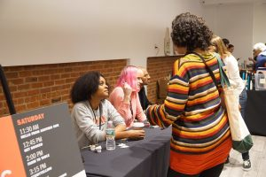 Left to right: Authors Alyssa Cole, Charlie Jane Anders, and Rumaan Alam sign books and chat with attendees after their panel.